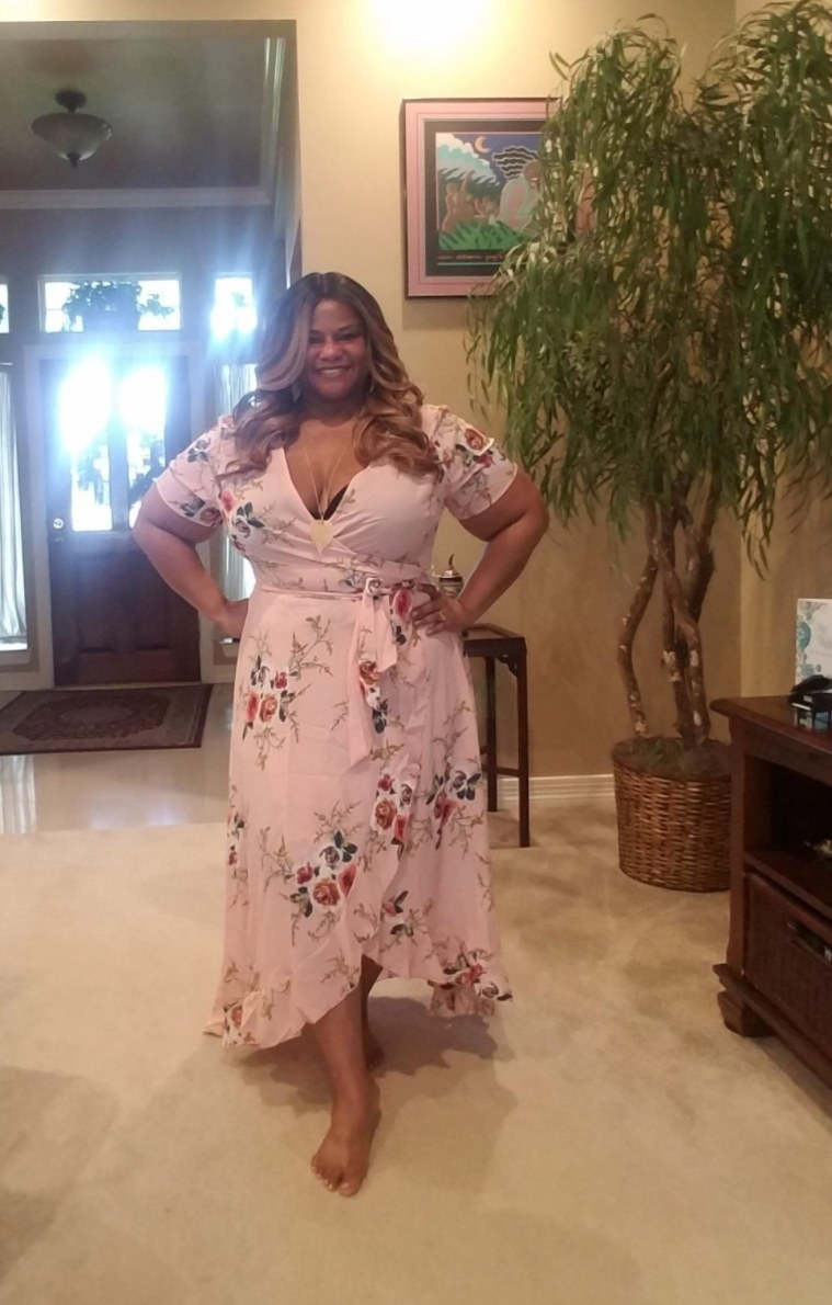 Reviewer wearing pink floral midi dress