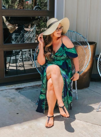 Reviewer sitting in green leaf print maxi dress with floppy hat