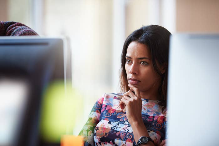 A woman looking thoughtfully at her work computer screen