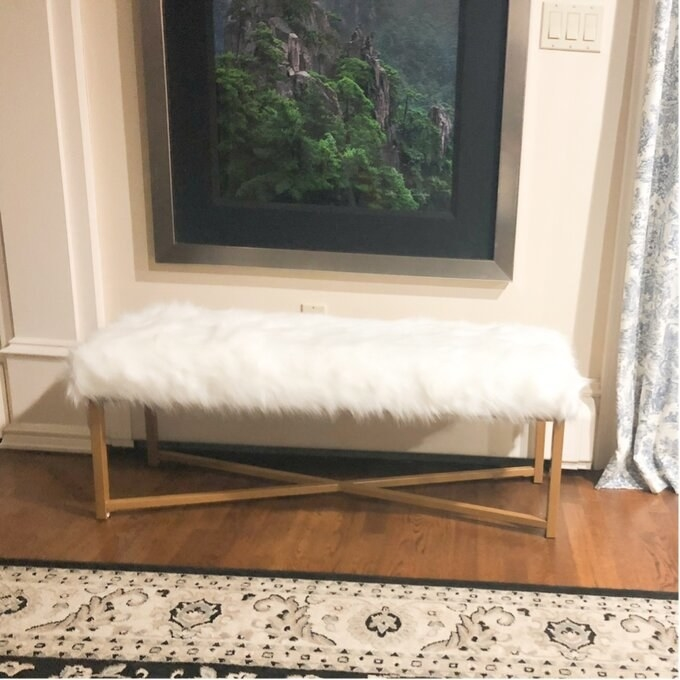 White furry rectangular bench with X-shaped gold legs