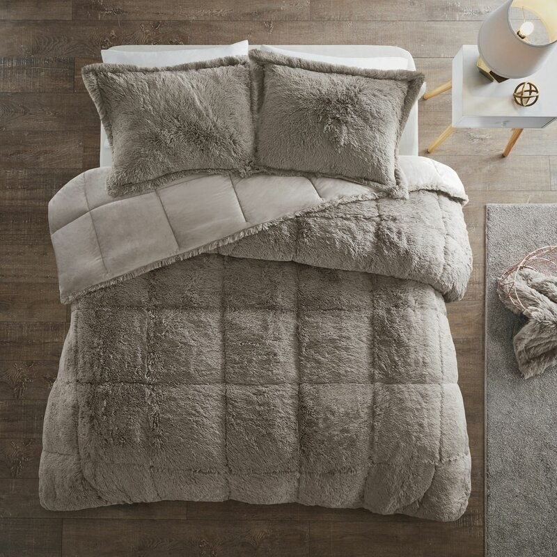 Two taupe pillows and taupe comforter with square indentions