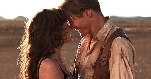 Evie and Rick touch noses and smile while standing in the desert