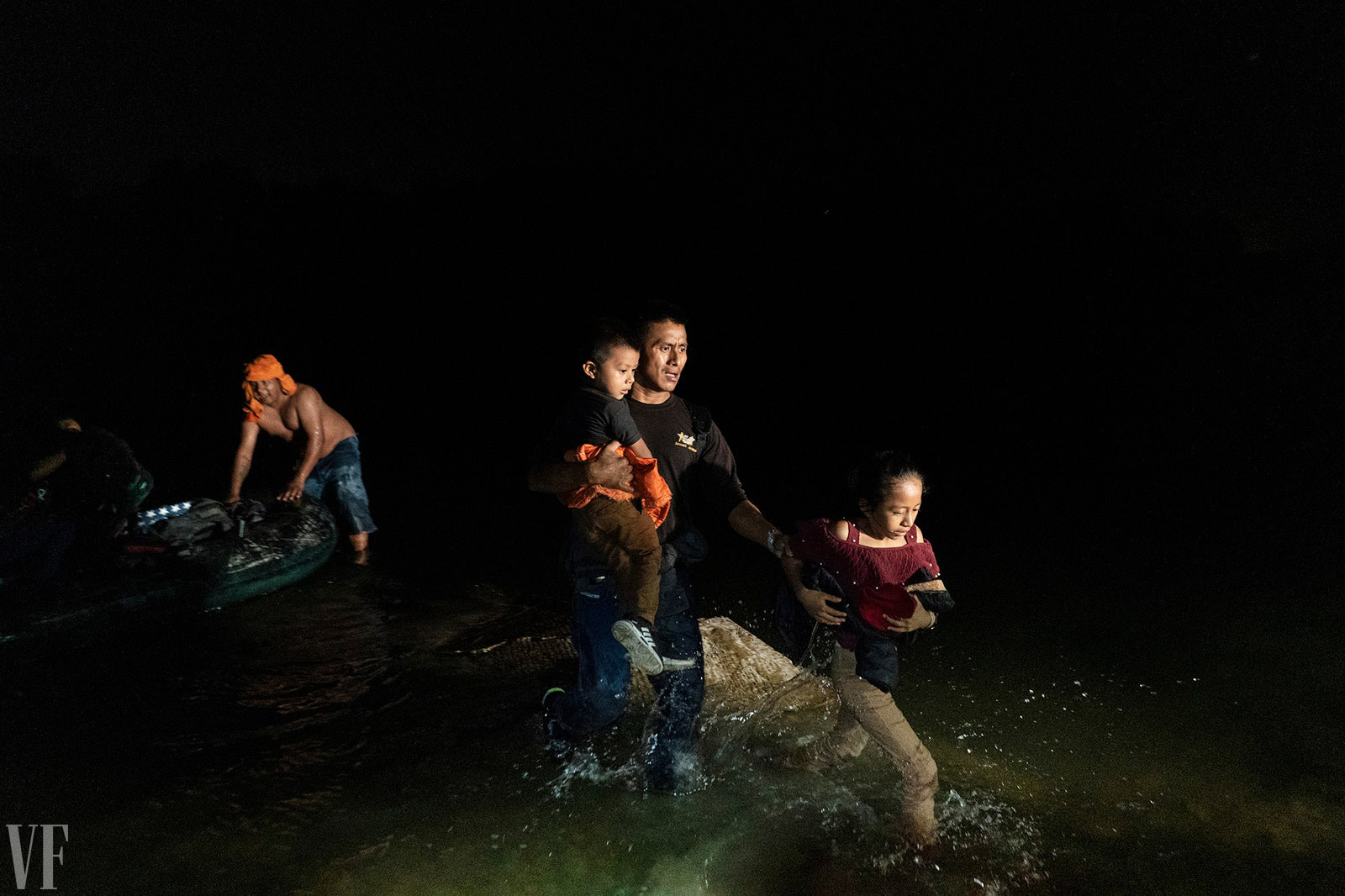 A father and two children get out of a boat at the border