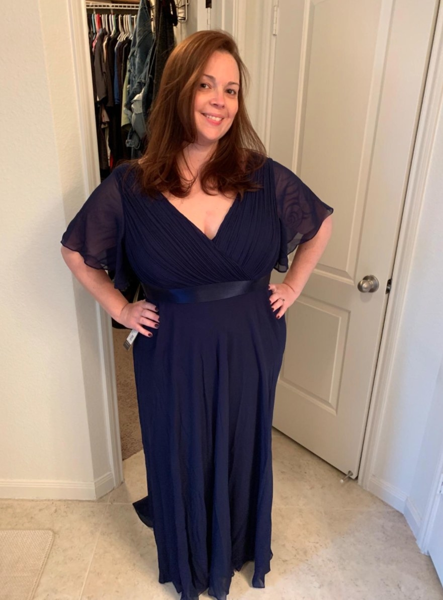 Reviewer posing in blue dress with sheer short sleeves