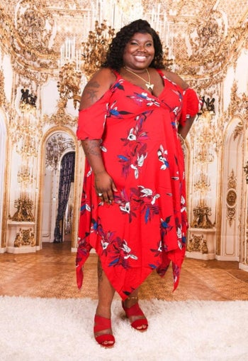 Reviewer wearing red floral dress and posing