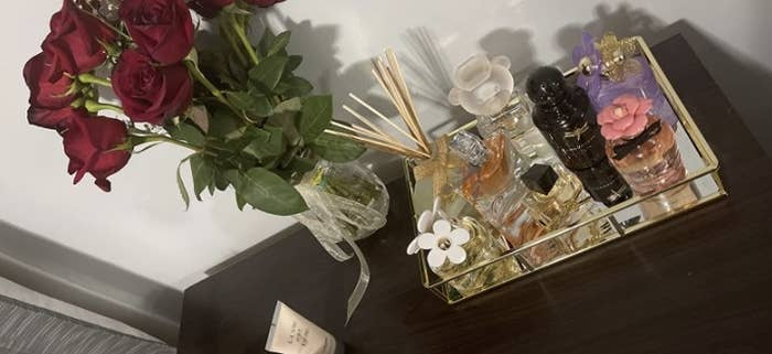 a reviewer showcasing the tray filled with luxury perfumes