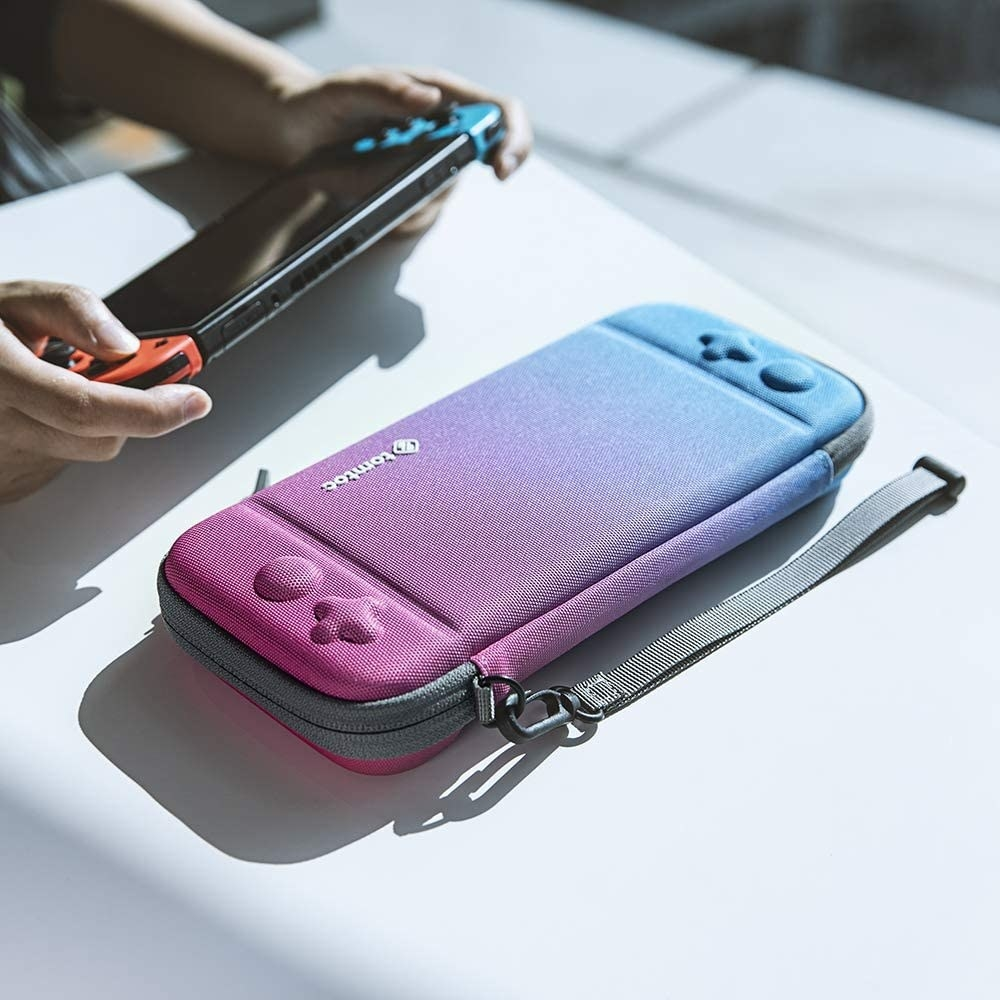 The case on a table in front of a person playing with their Switch