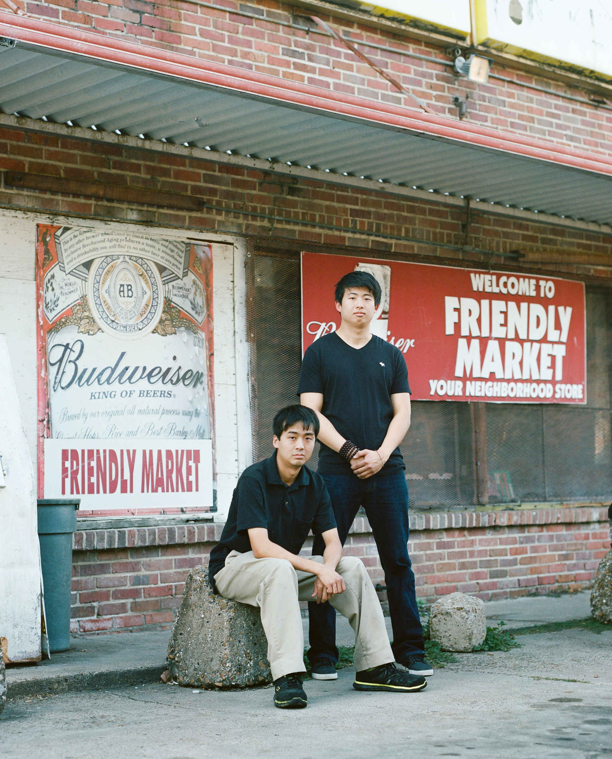 Two men sit in front of a small store with Budweiser signs and a sign saying Your Friendly Neighborhood Market