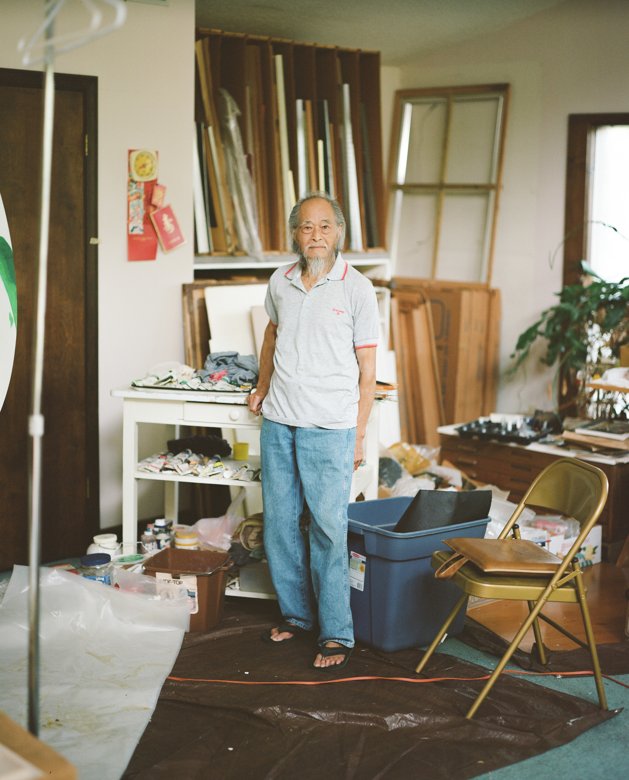 An older man in jeans and flip flops stands in a studio