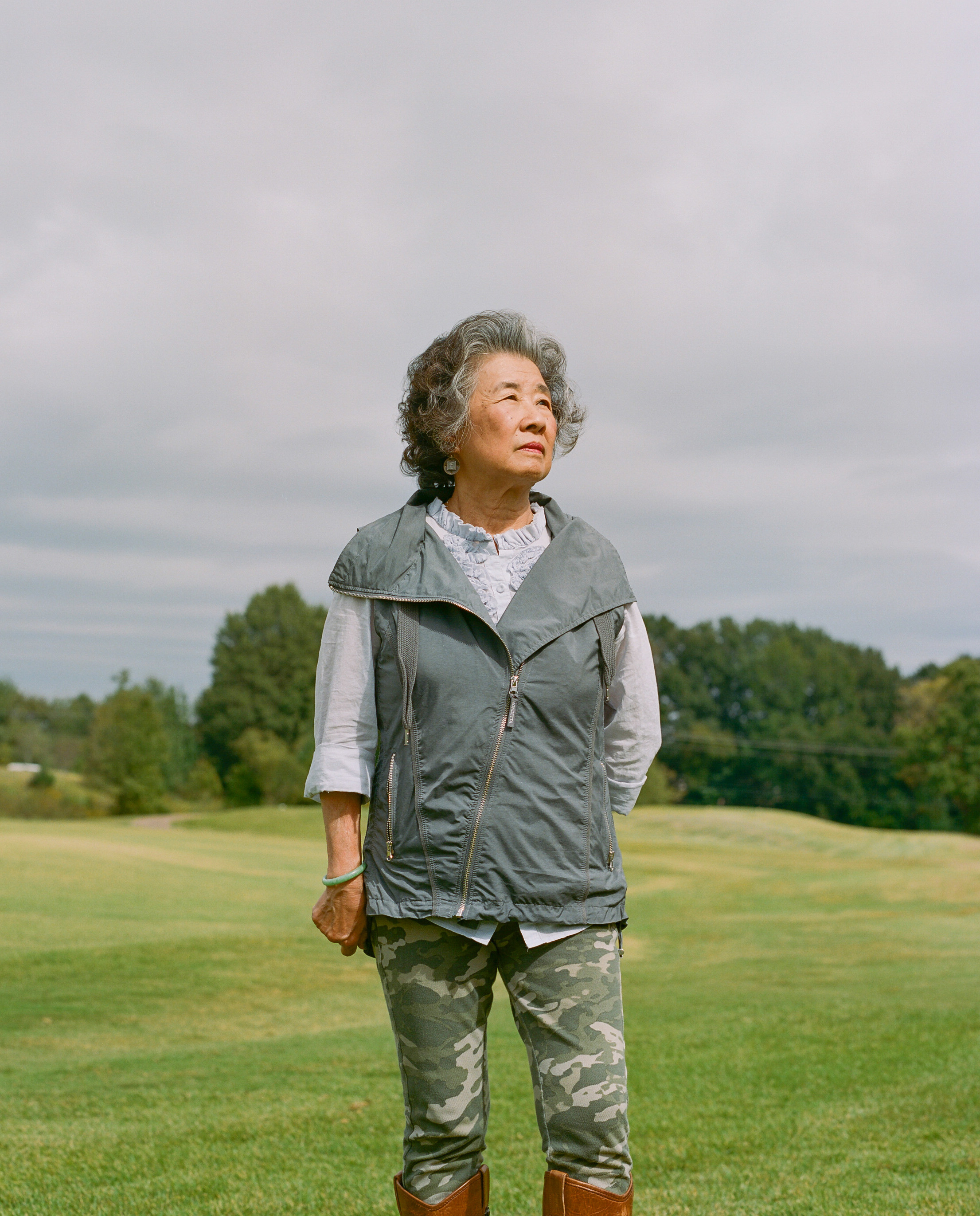 An older woman stands in a field wearing camo pants