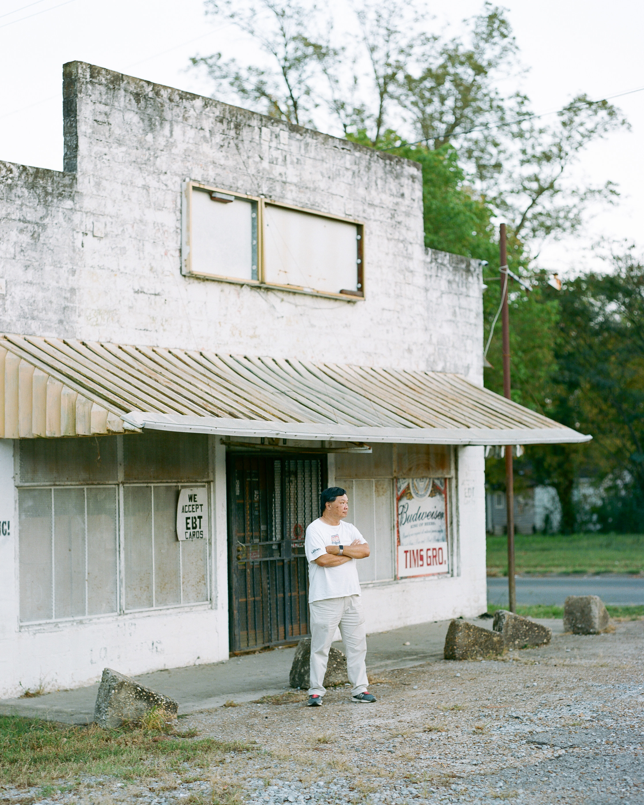 A man stands in front of an abandoned storefront