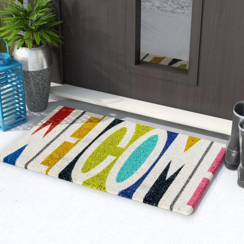 """rainbow-tone doormat that says """"welcome"""" in block white lettering"""