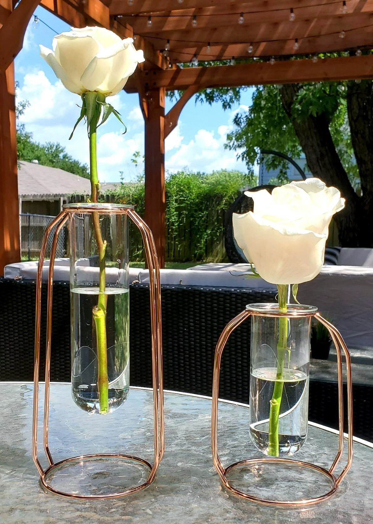 Reviewer vases on table with flowers in them