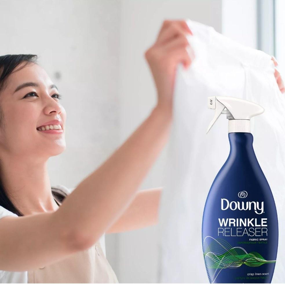 Model holding white linen with Downy spray image in bottom right corner