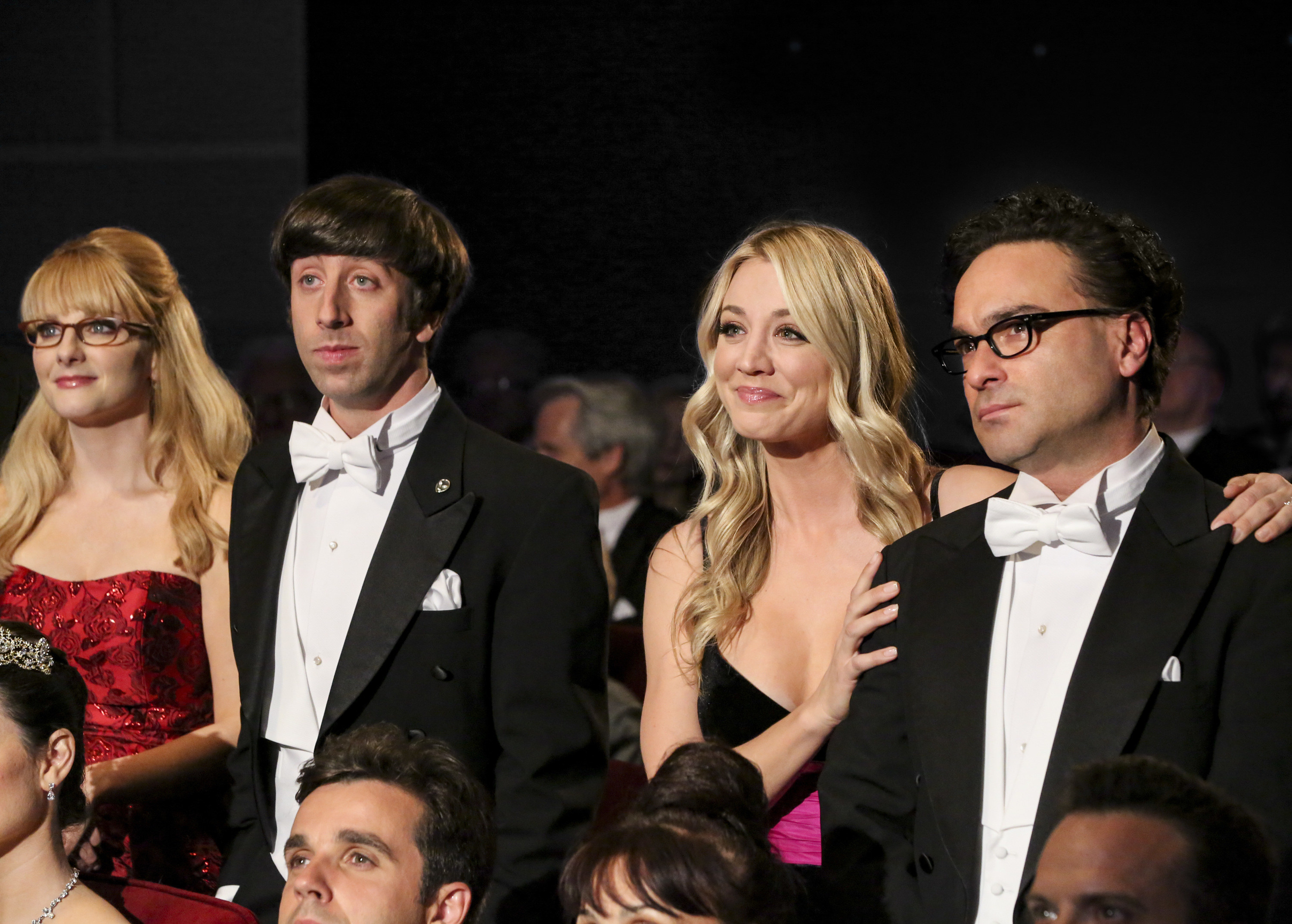 Leonard, Penny, Howard, and Bernadette stand in the audience at a black-tie event