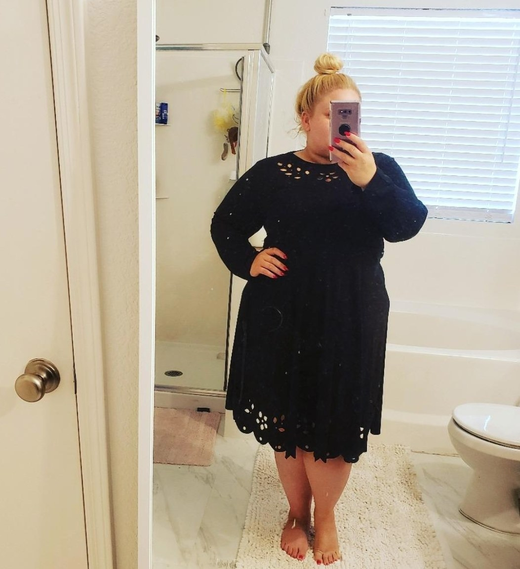 reviewer wearing long-sleeve, knee-length dress with laser cut details