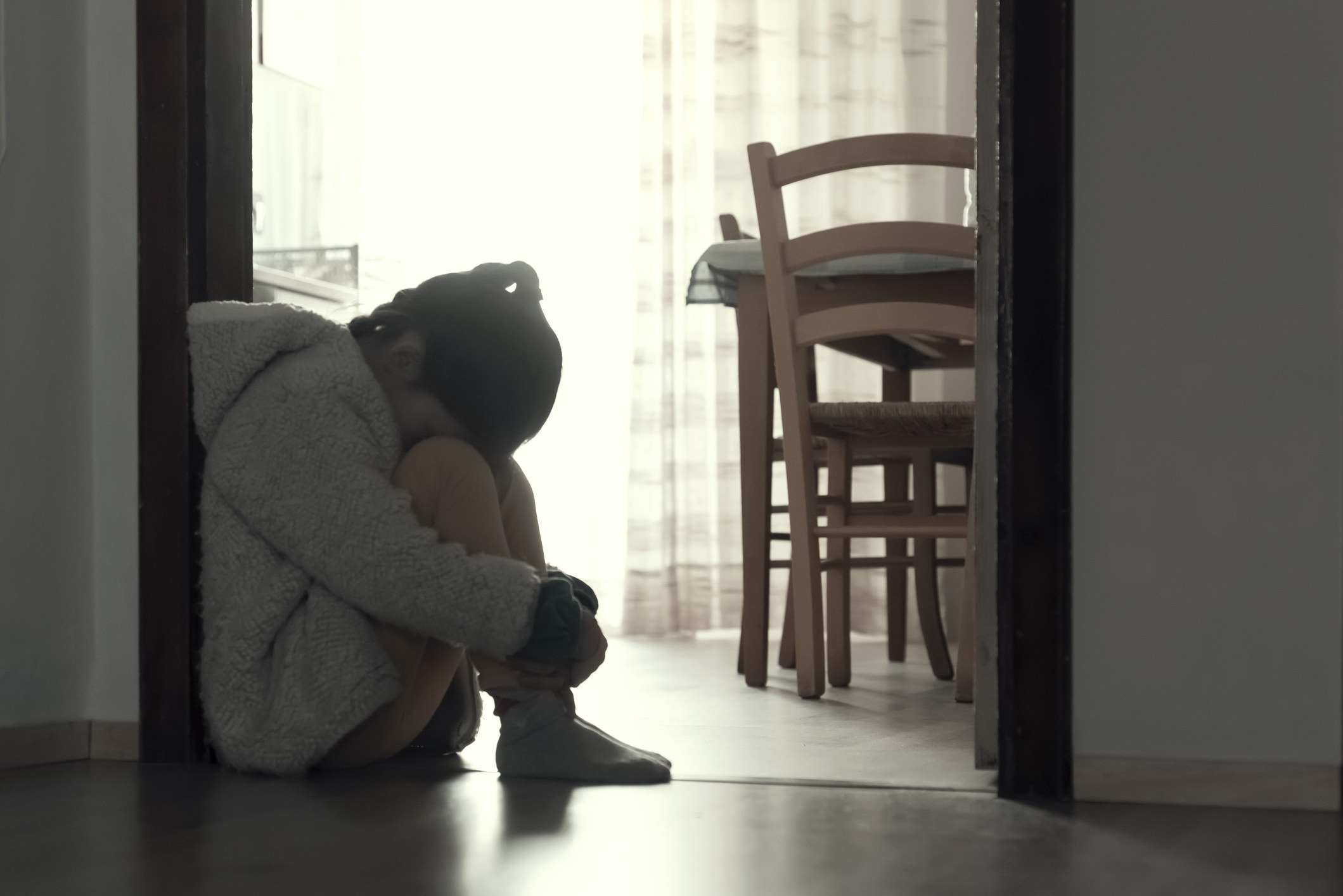 A child crouched in the doorway looking upset
