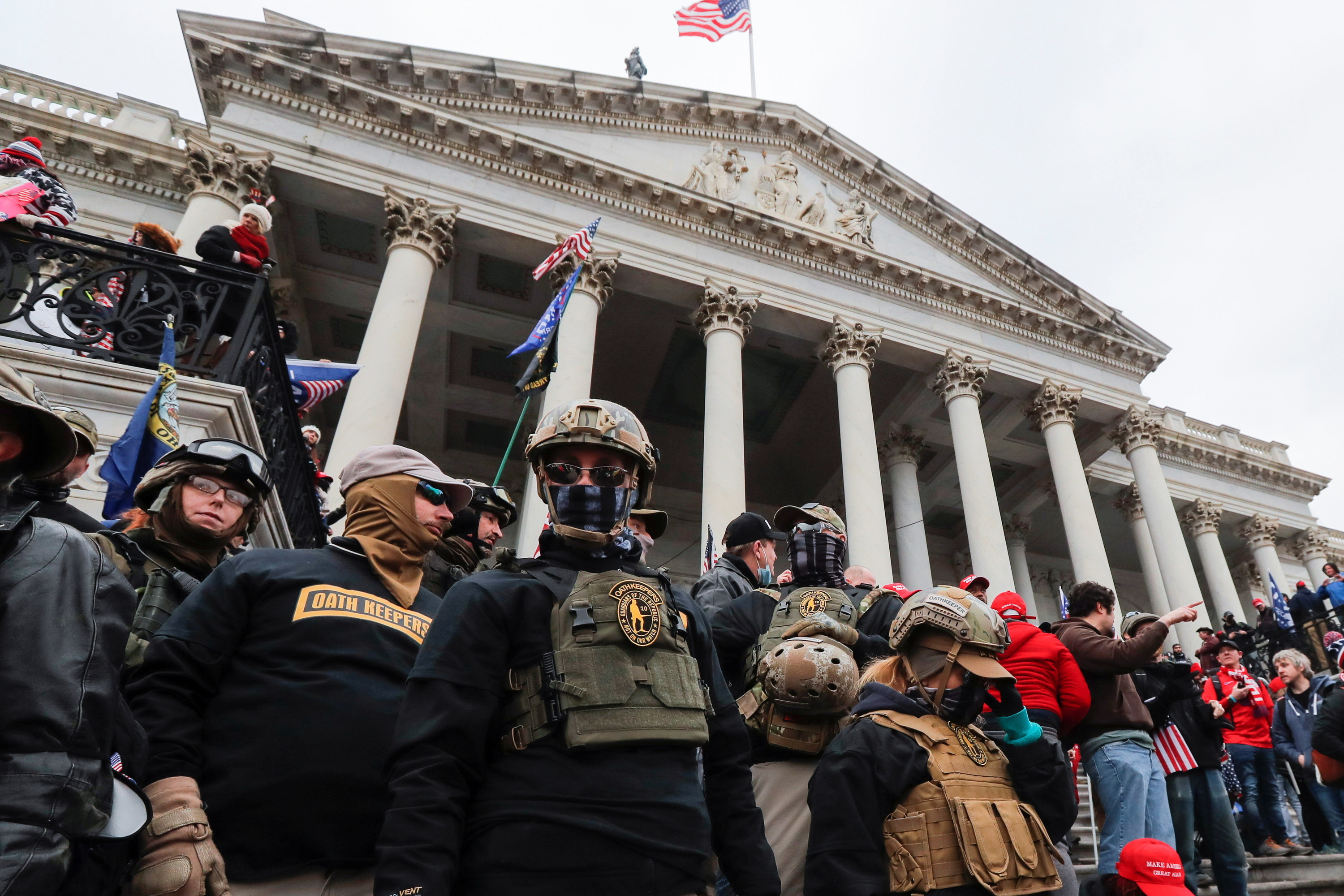 People wearing military-style tactical gear stand among a crowd outside the Capitol building in DC