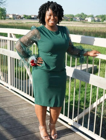 Reviewer in green fitted dress with sheer sleeves