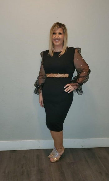 Reviewer in black fitted dress with sheer sleeves