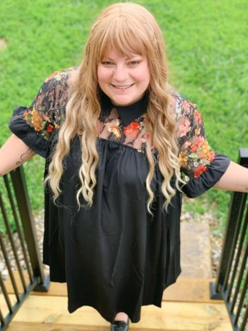 Reviewer wearing black dress with sheer floral embroidered top panel and collar
