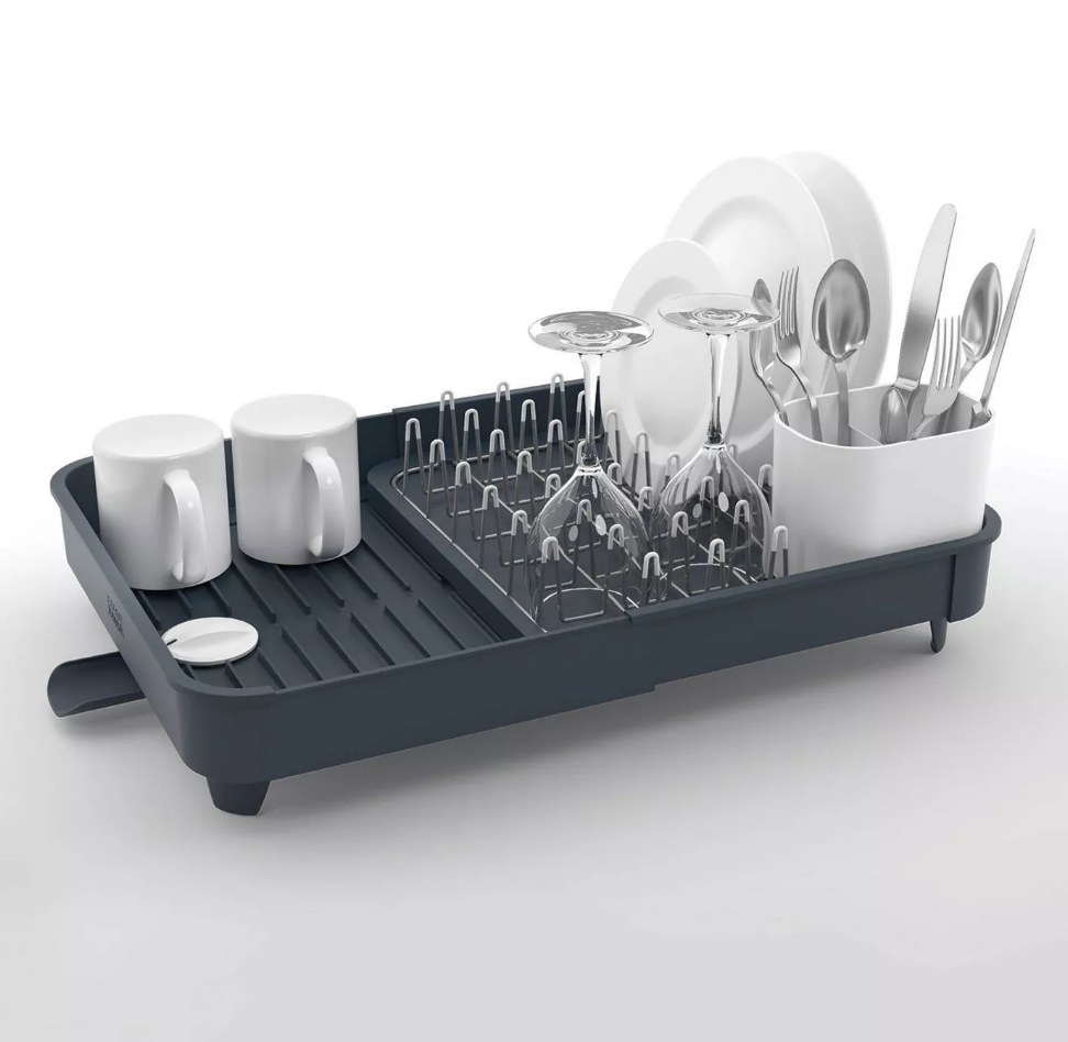 Gray extendable drying rack with dishes on it