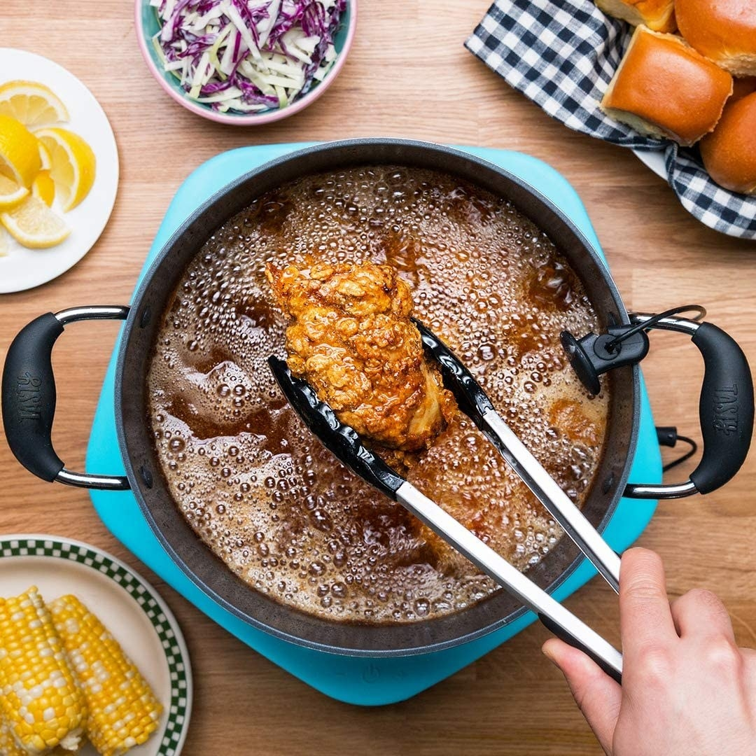a person frrying chicken in a pot on the One Top device