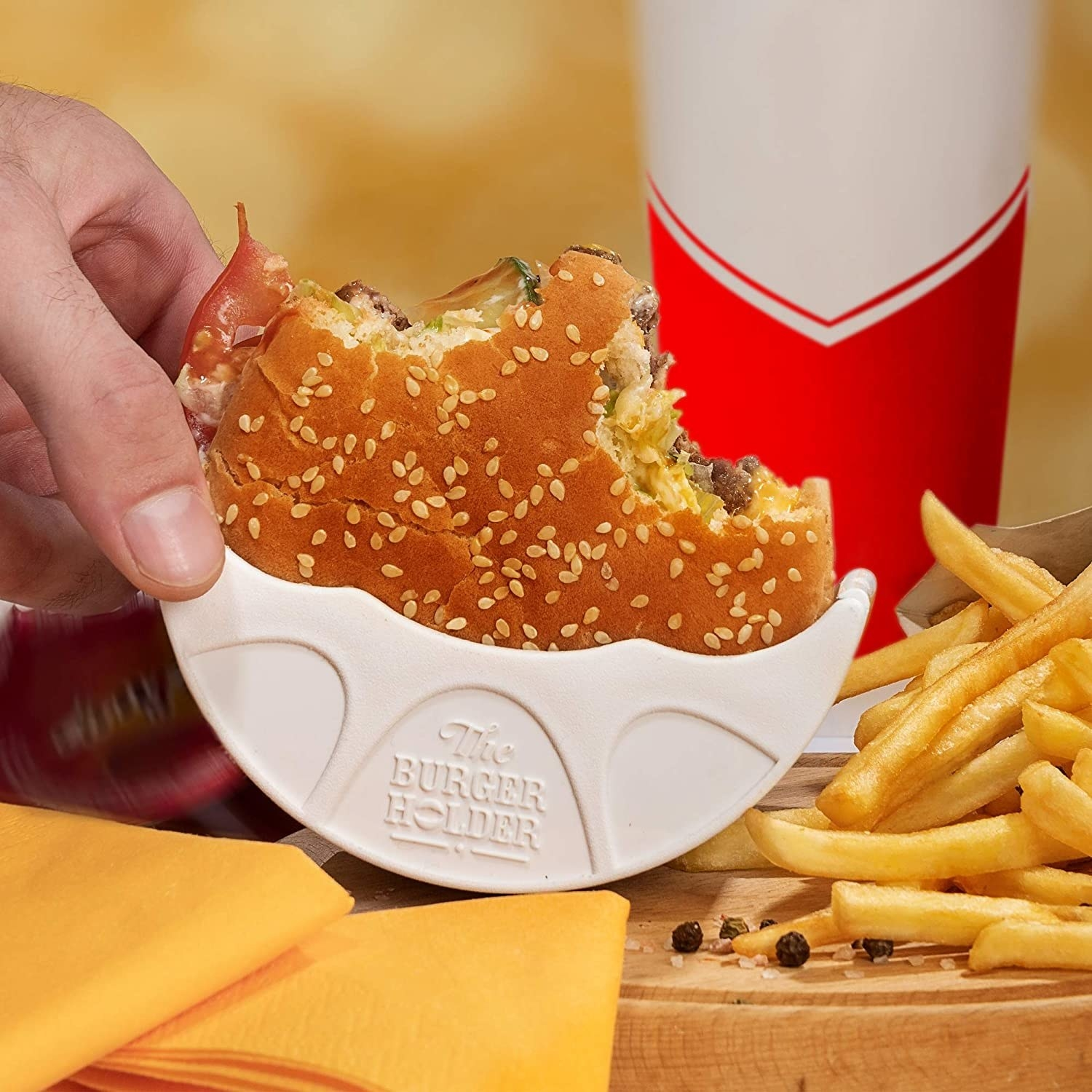 A person holding a burger in the burger holder