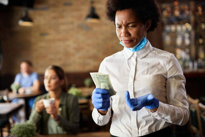 A waitress looking at her tip with confused look on her face