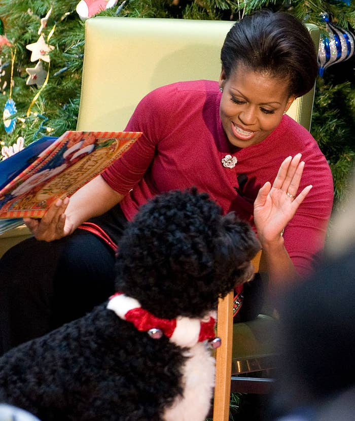 Mrs. Obama reading a children's book as Bo walks by