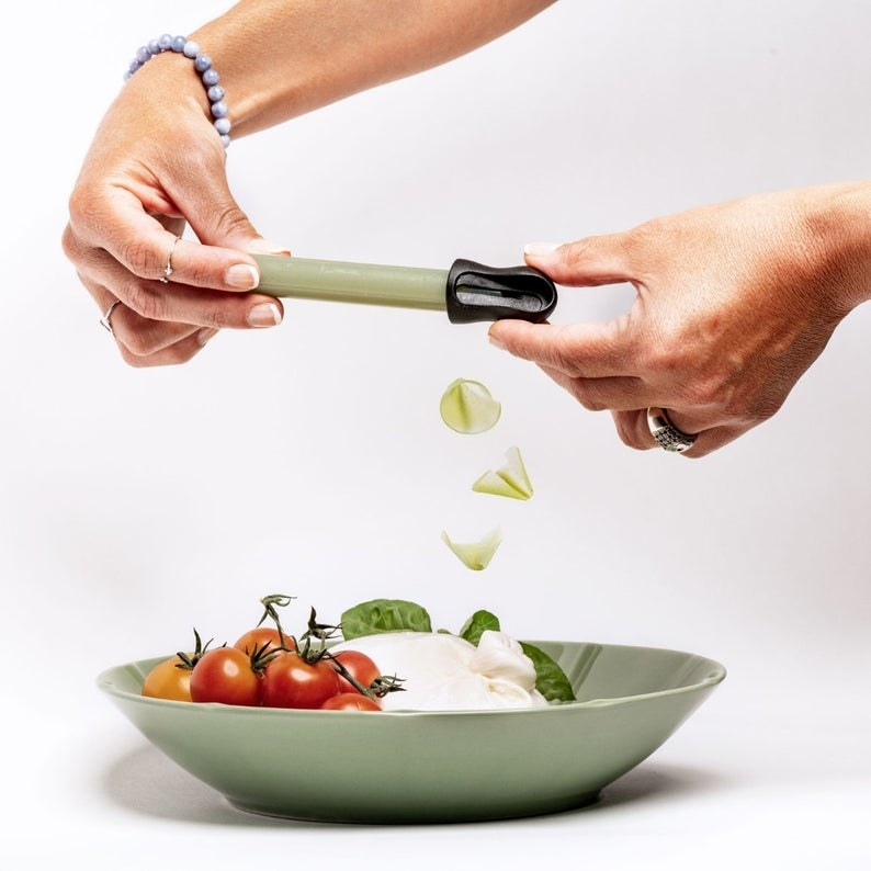 Hand shaving the thyme seasoning crayon on a plate of mozzarella and tomatoes