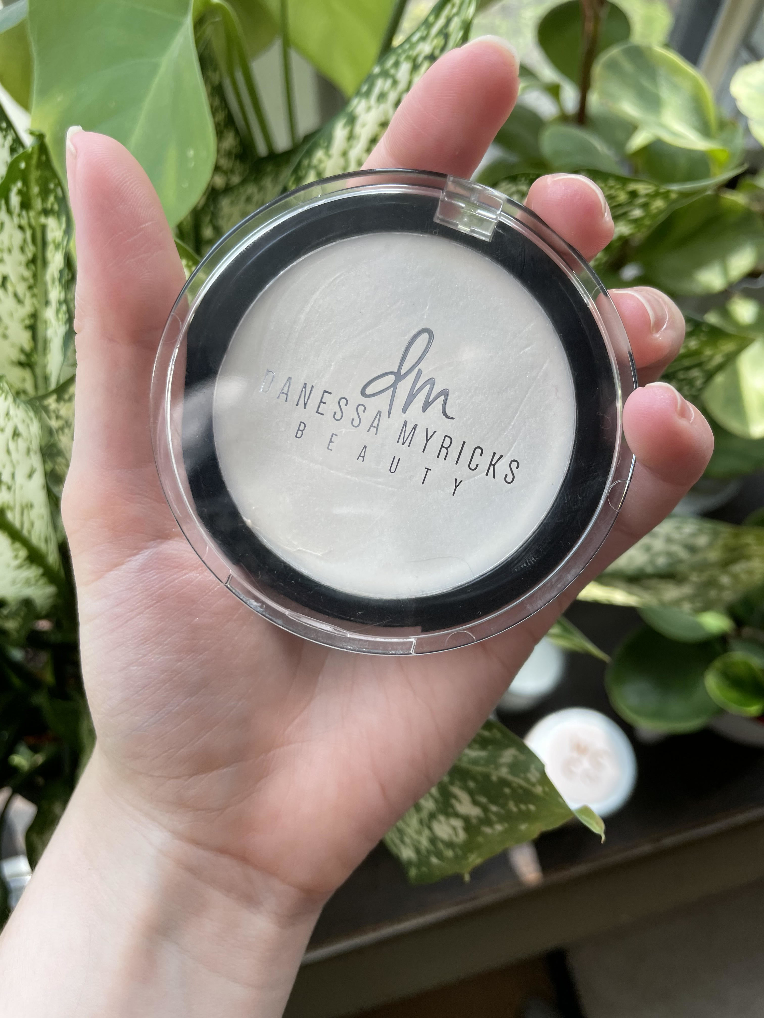 A person holding the compact of highlighter in front of plants