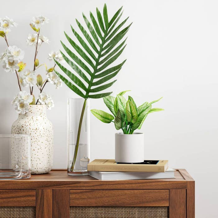 An artificial plant in a white pot on top of a console table