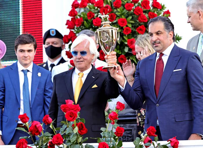 A man with white hair and a yellow tie holds up the Kentucky Derby trophy