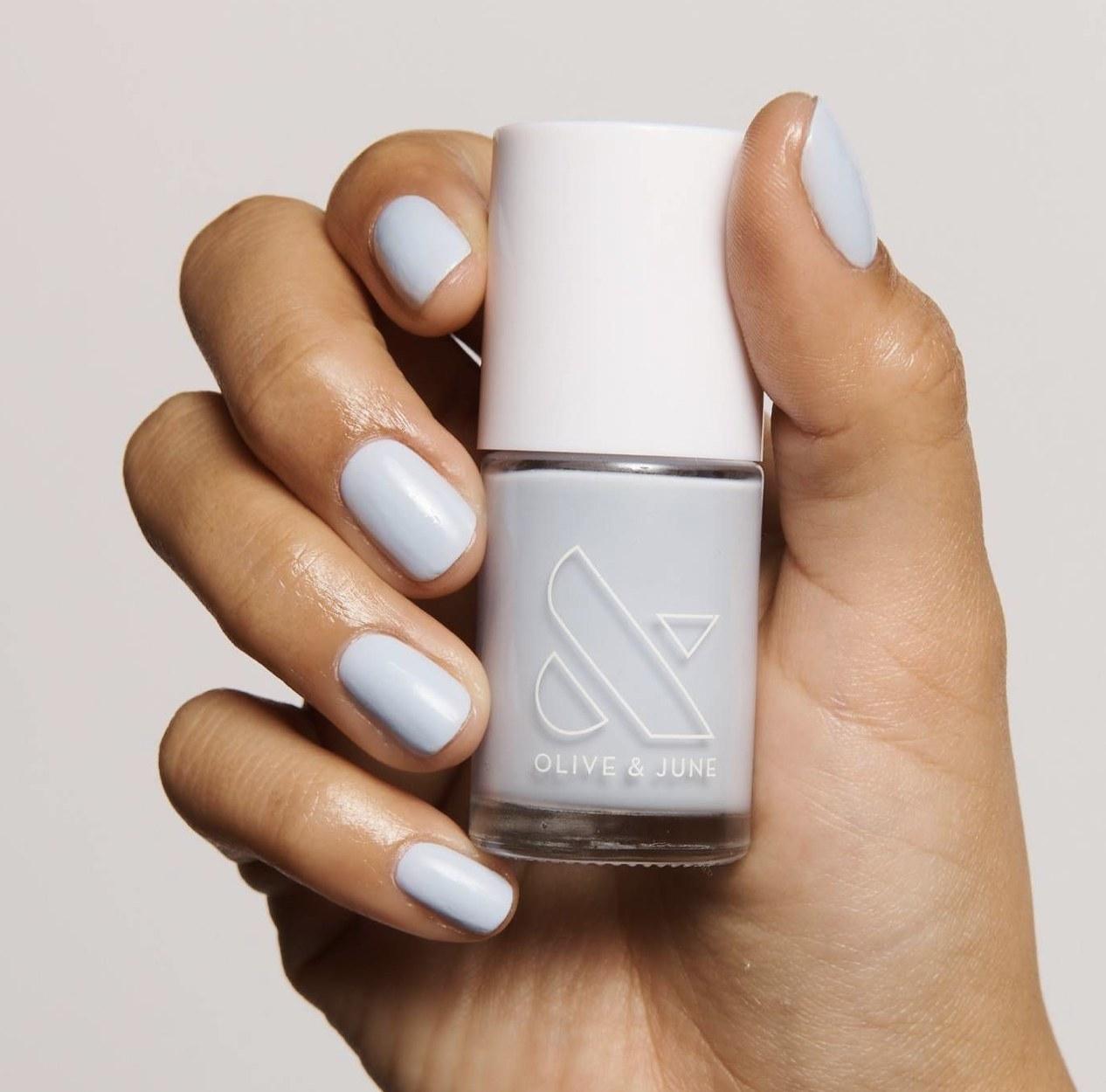 A woman's wearing a light blue manicure