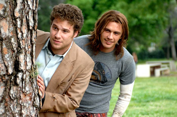 Rogen and Franco look from behind a tree in Pineapple Express