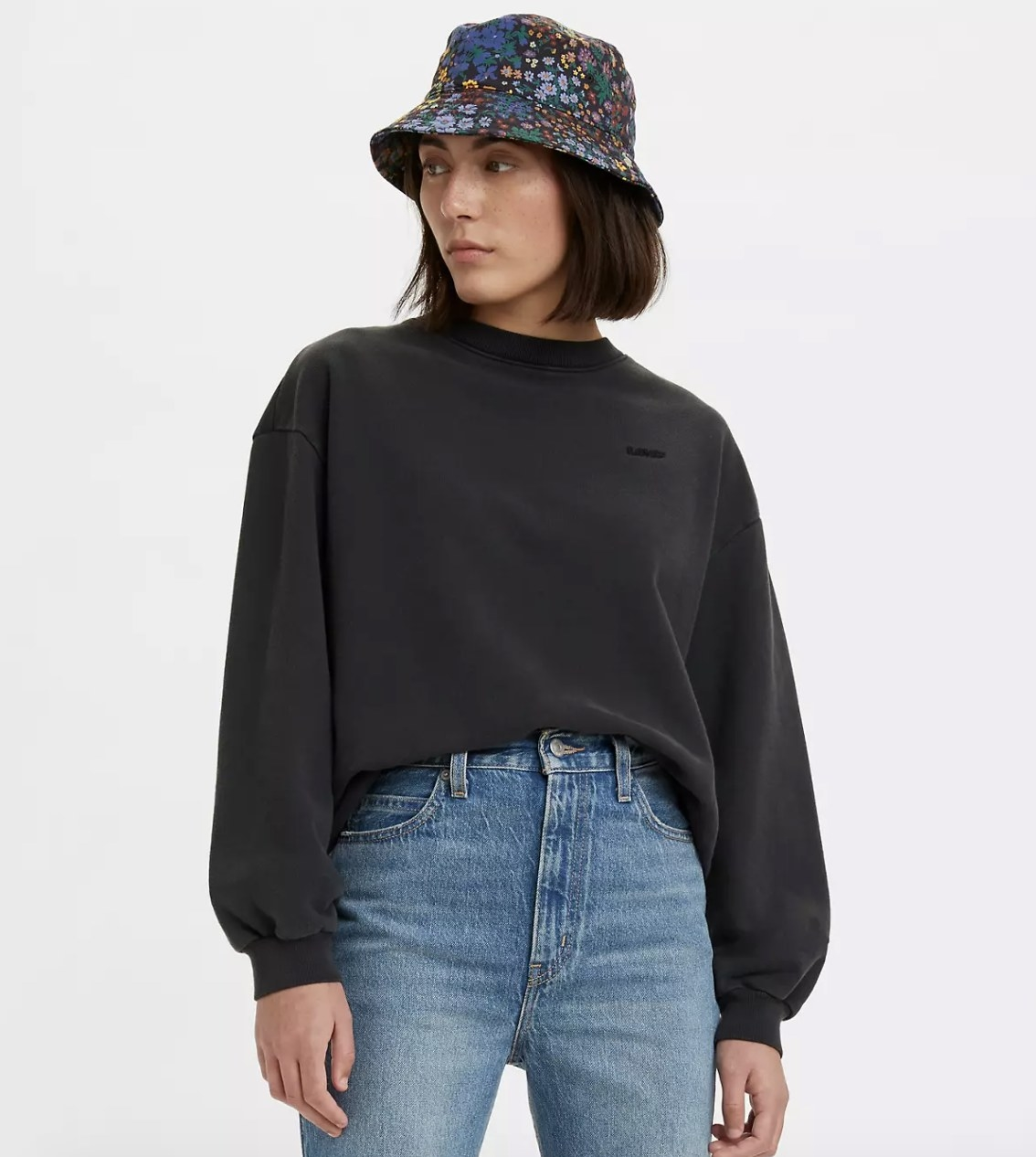 model wearing the crewneck sweatshirt in black with jeans and a floral bucket hat