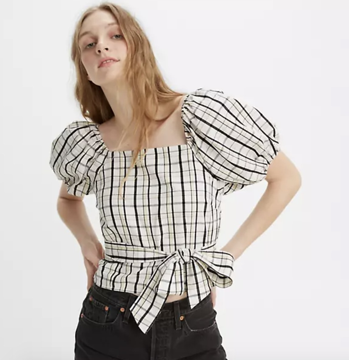 model wearing the top in white plaid with black jeans