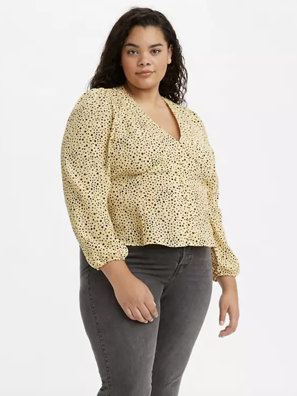 model wearing the top in yellow with black polka dots