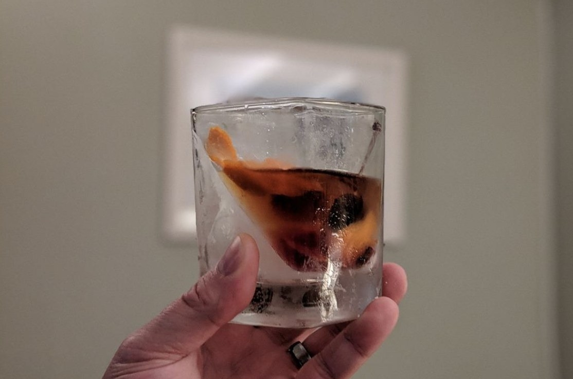 reviewer holding up the glass with half ice, half whiskey