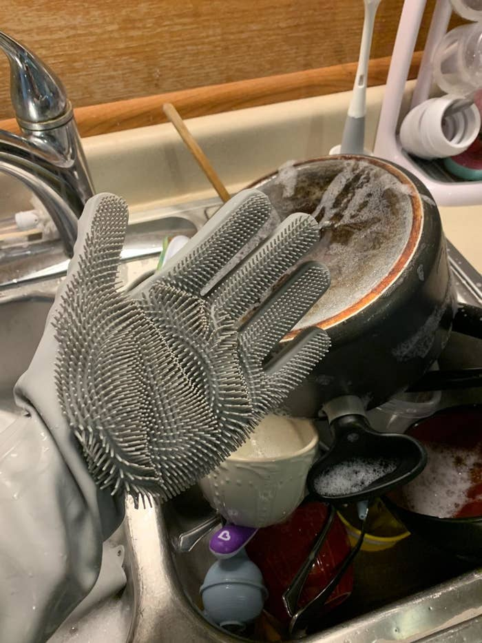 Reviewer wearing the gloves while washing dishes with right hand facing up, showing the bristols on it