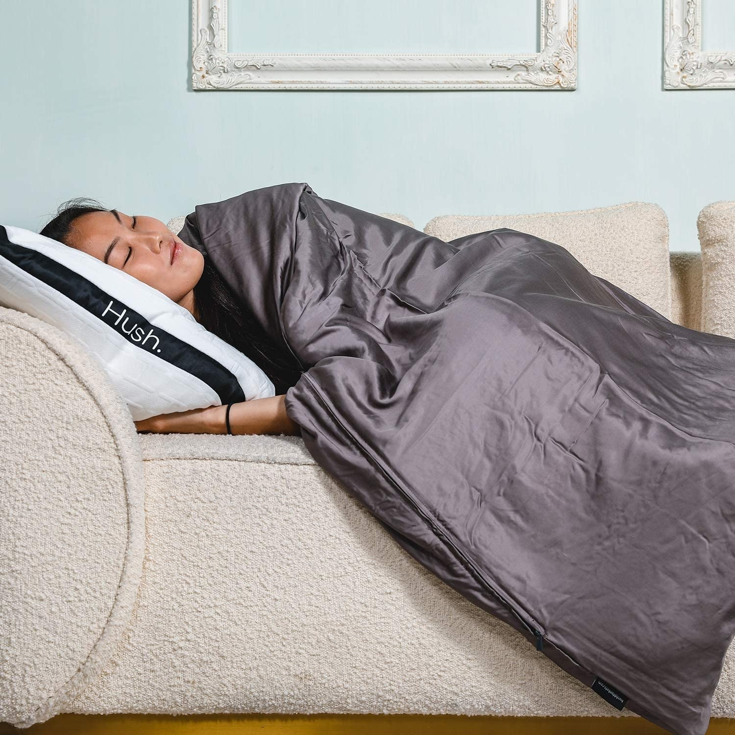 A person sleeping on a couch under the blanket