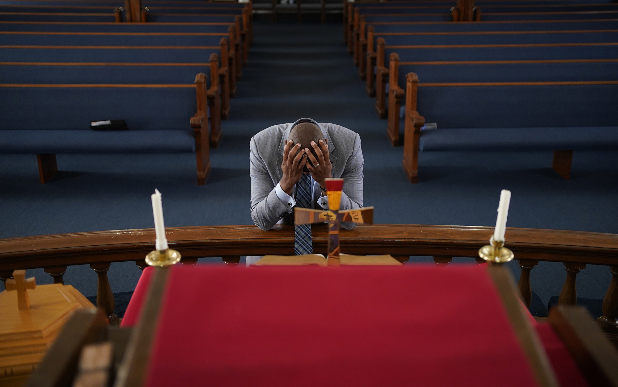 A man prays at an altar with his head in his hands