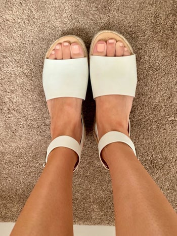 a reviewer wearing the sandals in white