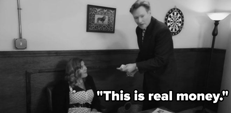 Conan handing woman money