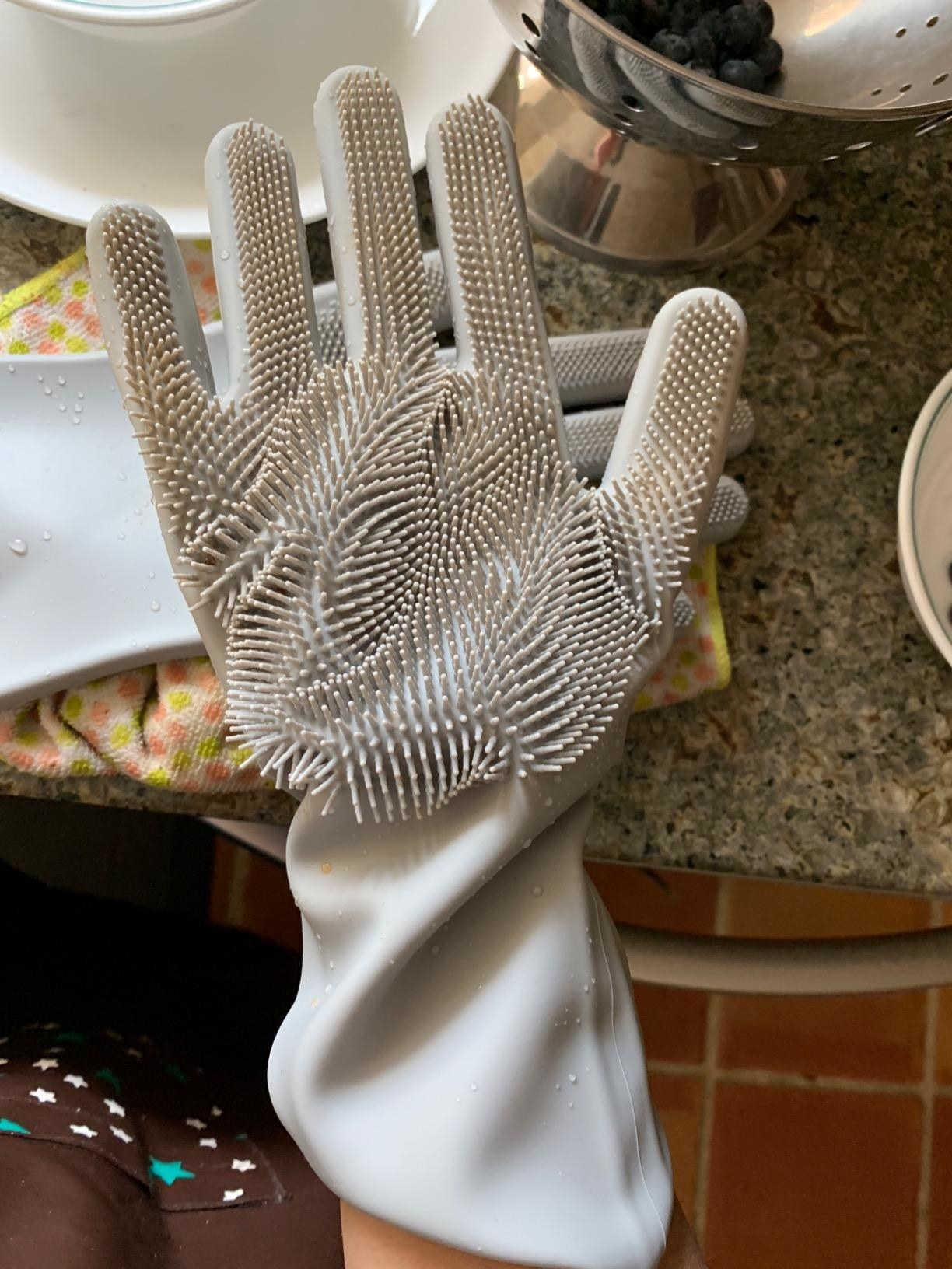 reviewer showing a grey glove with scrubbing bristles on it