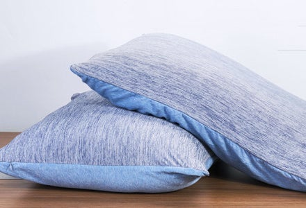 Two pillows with the pillow cases on them on a table