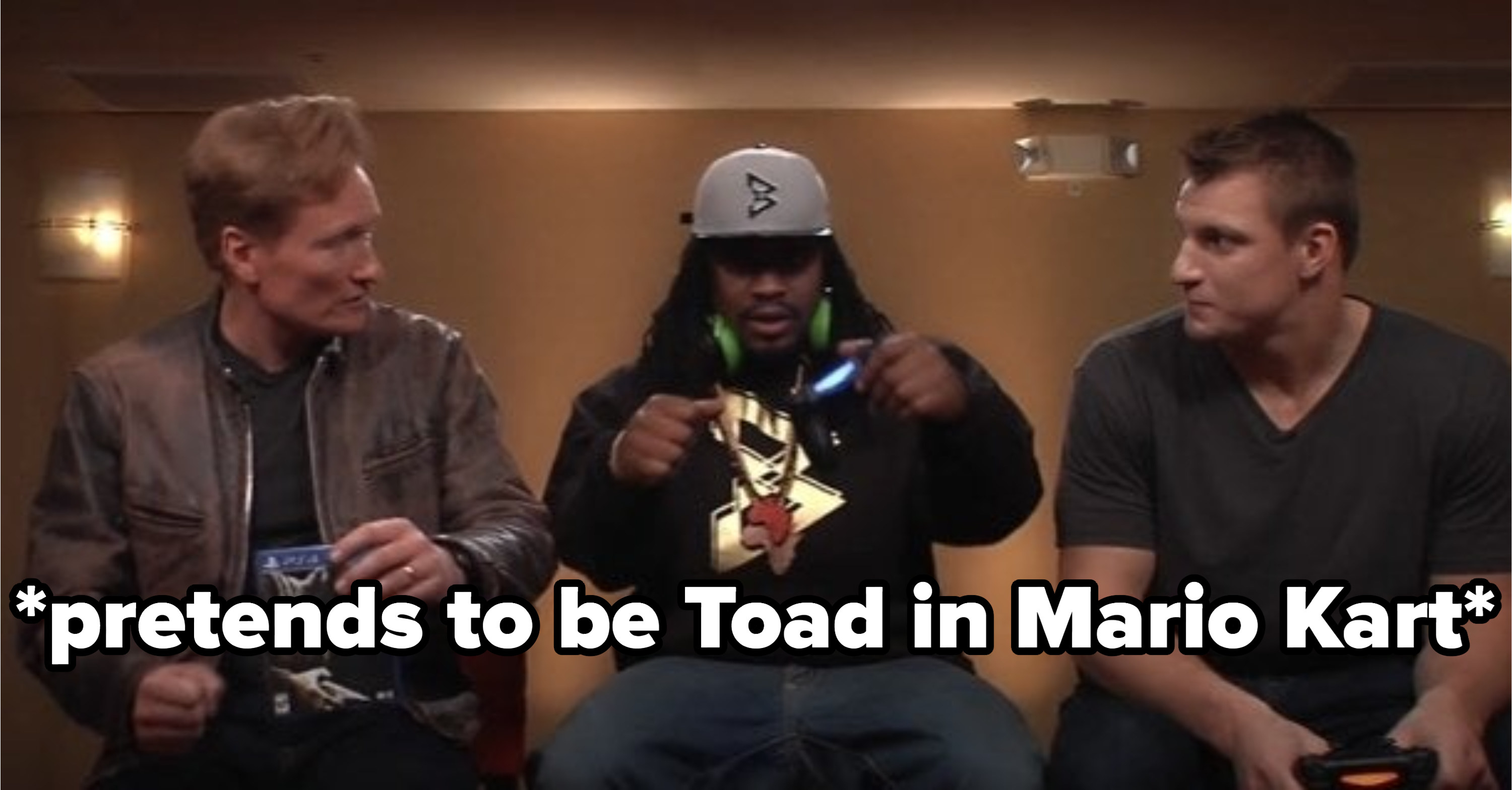 Conan, Marshawn Lynch, and Rob Gronkowski sitting on stools and playing video games