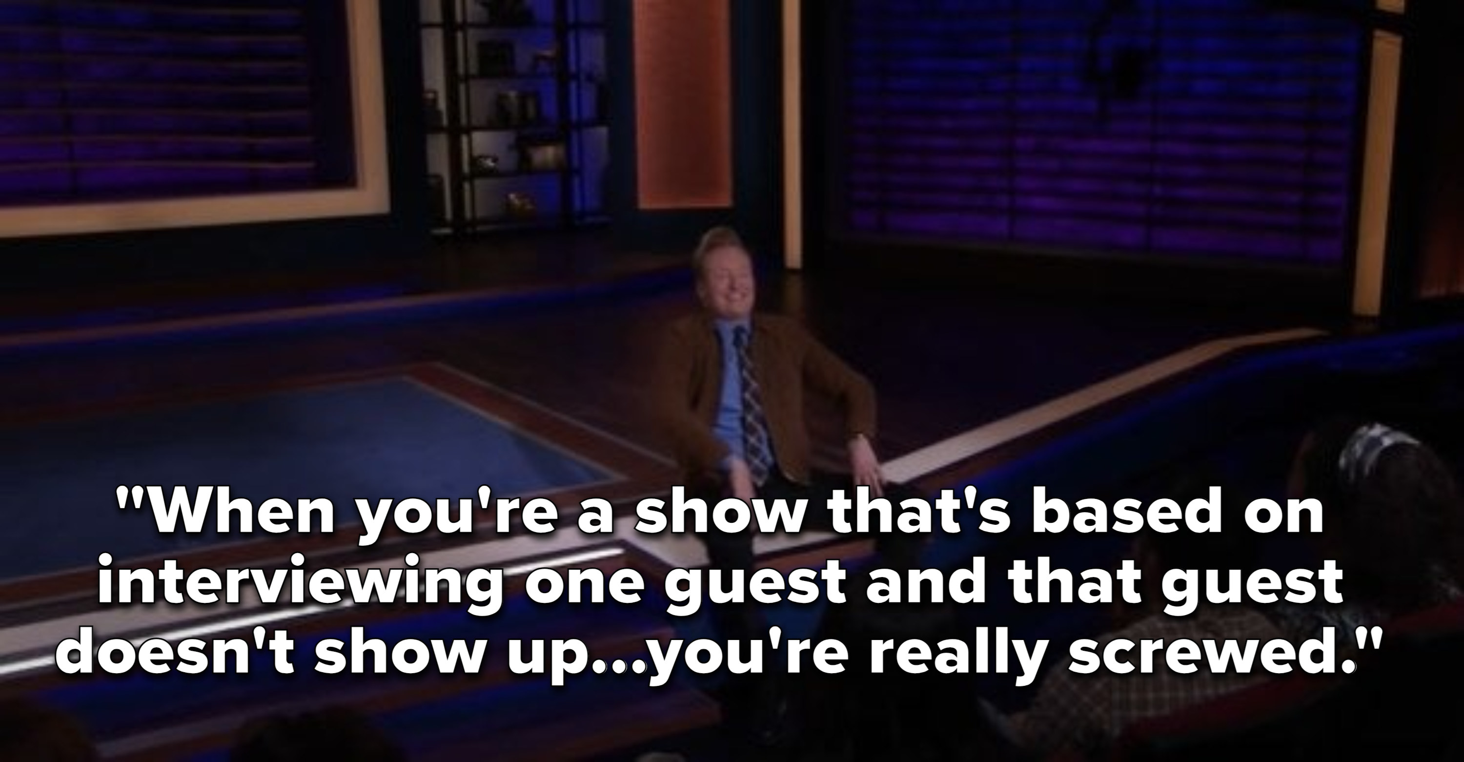 Conan sitting on the lip of the stage