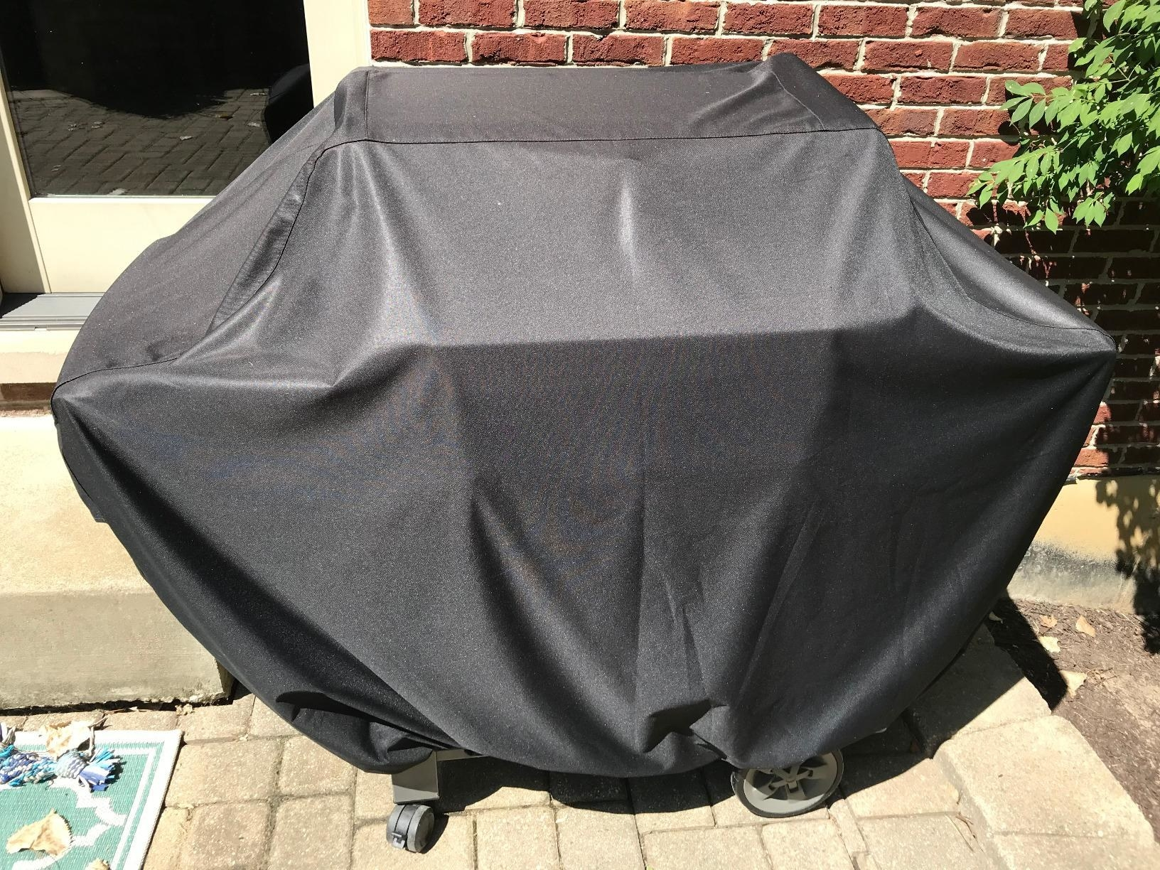 a reviewer's grill covered in a black tarp-like cover